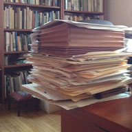 Tall pile of papers on edge of desk